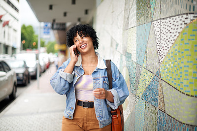 Buy stock photo Shot of a young woman talking on a cellphone while walking through the city