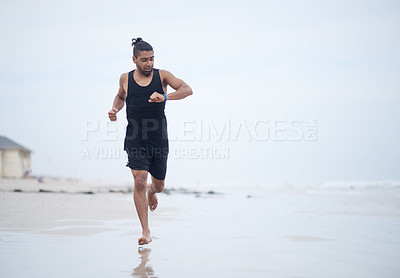 Buy stock photo Full length shot of a handsome and sporty young man running outdoors on the beach