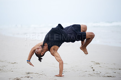 Buy stock photo Full length shot of a handsome and athletic young man dancing outdoors on the beach