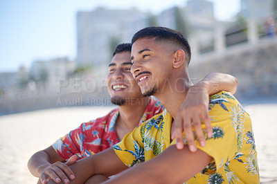 Buy stock photo Cropped shot of an affectionate gay couple sitting together and bonding during a day out on the beach