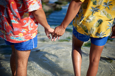Buy stock photo Cropped shot of an unrecognizable gay couple holding hands while walking through a tidal pool at the beach