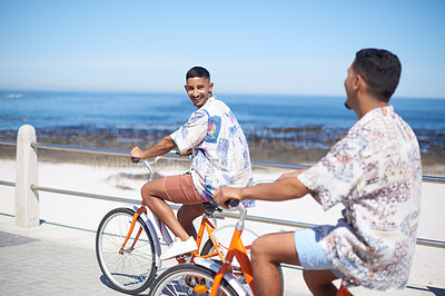 Buy stock photo Cropped shot of a young gay couple bonding together and riding bicycles along the promenade during a day out