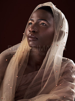 Buy stock photo Studio shot of an attractive young woman posing in traditional African attire against a black background