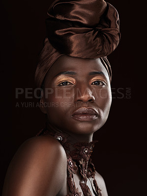 Buy stock photo Studio portrait of an attractive young woman posing in traditional African attire against a black background