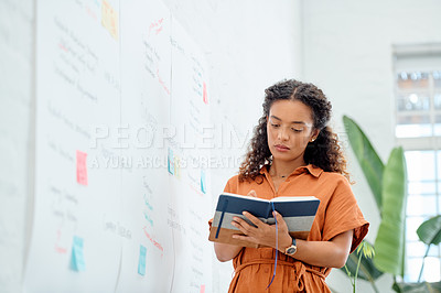 Buy stock photo Shot of a young businesswoman holding a notebook while brainstorming with notes on a wall in an office