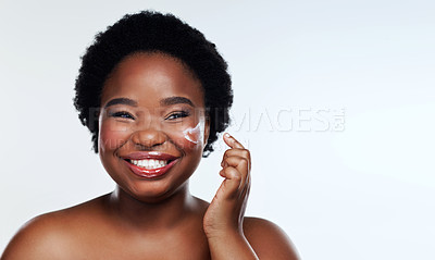 Buy stock photo Studio shot of a beautiful young woman applying moisturiser to her face against a gray background