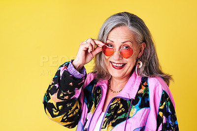 Buy stock photo Portrait of a confident and stylish senior woman wearing sunglasses posing against a yellow background