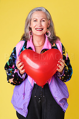 Buy stock photo Portrait of a confident and stylish senior woman holding a heart shaped balloon against a yellow background