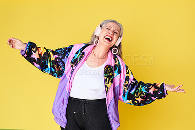 Buy stock photo Cropped shot of a cheerful and stylish senior woman listening to music on headphones against a yellow background