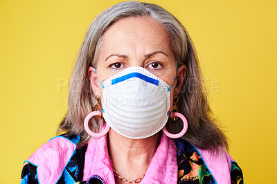 Buy stock photo Portrait of a quirky senior woman wearing a N95 face mask against a yellow background