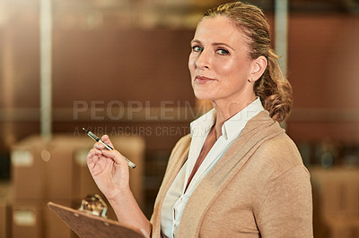Buy stock photo Cropped portrait of an attractive mature supervisor standing alone in a warehouse and using a clipboard for stocktaking