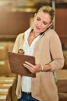 Buy stock photo Cropped shot of an attractive mature supervisor holding a clipboard while talking on her cellphone in a warehouse