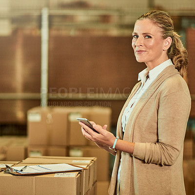 Buy stock photo Cropped portrait of an attractive mature supervisor standing alone and using her cellphone while doing a stocktake in a warehouse