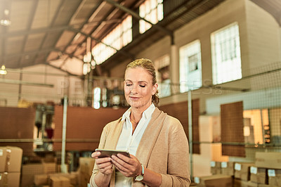 Buy stock photo Cropped shot of an attractive mature supervisor standing alone and using her cellphone while doing a stocktake in a warehouse