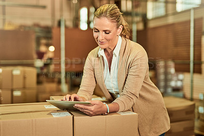 Buy stock photo Cropped shot of an attractive mature supervisor standing alone and using a tablet during a stocktake in a warehouse