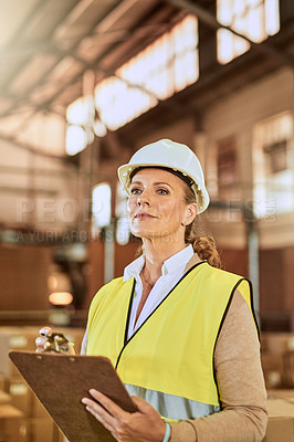 Buy stock photo Cropped shot of an attractive mature supervisor wearing a safety helmet and vest during a stock take in a warehouse