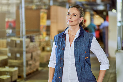 Buy stock photo Cropped shot of an attractive mature supervisor standing alone in a warehouse during the day