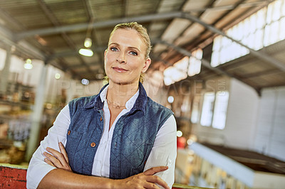 Buy stock photo Cropped portrait of an attractive mature supervisor standing alone in her warehouse with her arms folded