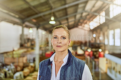 Buy stock photo Cropped portrait of an attractive mature supervisor standing alone in a warehouse during the day
