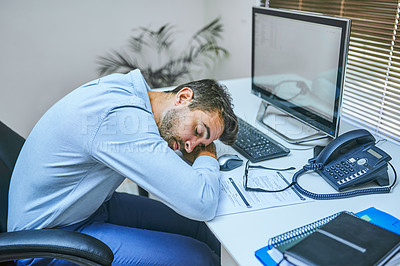 Buy stock photo Shot of a businessman sleeping with his head on his desk