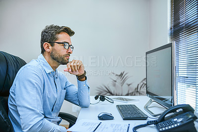 Buy stock photo Cropped shot of a businessman sitting at his desk with his computer in front of him