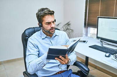 Buy stock photo Shot of a call center agent wearing his headset while sitting in the office
