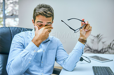 Buy stock photo Cropped shot of a businessman looking exhausted while sitting at his desk