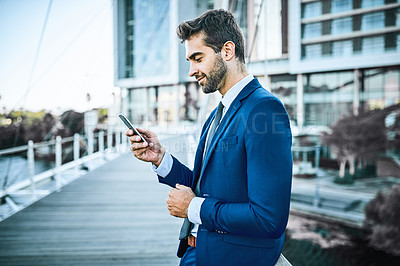Buy stock photo Shot of a businessman using his cellphone while standing on a bridge