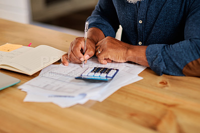 Buy stock photo Cropped shot of an unrecognizable mature man calculating and going over his finances at home
