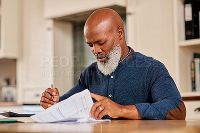 Buy stock photo Cropped shot of a mature man going over some paperwork at home