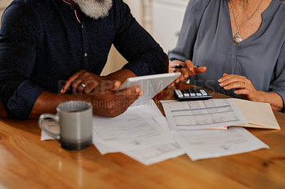 Buy stock photo Cropped shot of an unrecognizable senior couple using a digital tablet while going over bills and paperwork together at home