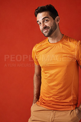 Buy stock photo Studio shot of a handsome young man posing against a red background