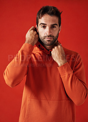 Buy stock photo Studio shot of a handsome young man wearing a hoody against a red background