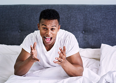 Buy stock photo Portrait of a handsome young man screaming and feeling frustrated while sitting on his bed at home