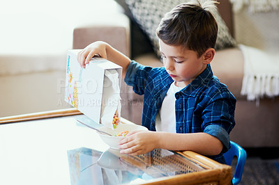 Buy stock photo Shot of an adorable little boy pouring cereal into a bowl at home