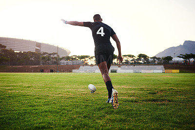 Buy stock photo Full length shot of an unrecognizable sportsman kicking a rugby ball during an early morning training session