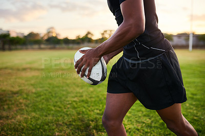 Buy stock photo Cropped shot of an unrecognizable sportsman standing alone and holding a rugby ball before an early morning practice