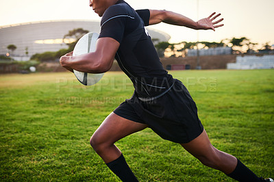 Buy stock photo Cropped shot of an unrecognizable sportsman running alone while holding a rugby ball during an early morning practice