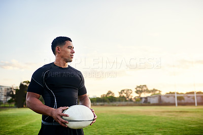 Buy stock photo Cropped shot of a handsome young sportsman standing alone and holding a rugby ball before an early morning practice