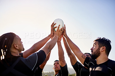 Buy stock photo Cropped shot of a handsome group of sportsmen holding a rugby ball together before playing rugby