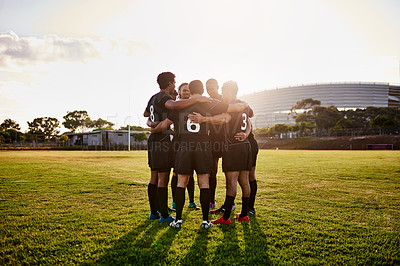 Buy stock photo Full length shot of a handsome group of sportsmen huddled together before playing rugby