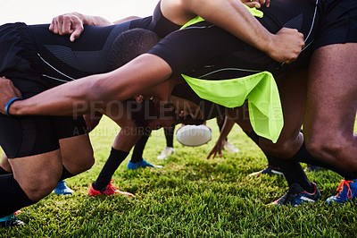Buy stock photo Cropped shot of a diverse group of sportsmen performing a scrum during a rugby game during the day