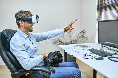 Buy stock photo Shot of a businessman sitting with his dog on his lap while wearing a virtual reality headset