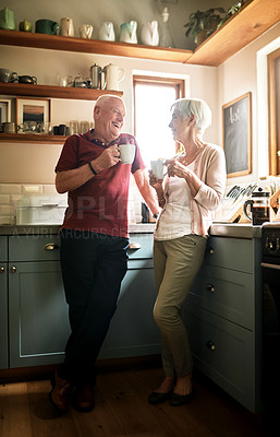 Buy stock photo Full length shot of an affectionate senior couple standing together in their kitchen and enjoying a cup of coffee