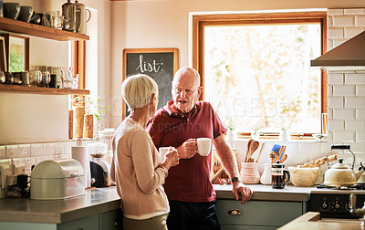 Buy stock photo Cropped shot of an affectionate senior couple standing together in their kitchen and enjoying a cup of coffee