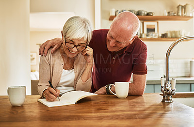 Buy stock photo Cropped shot of a happy senior man holding his wife while she writes in her notebook