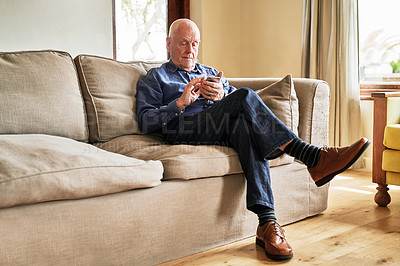 Buy stock photo Full length shot of a senior man sitting alone on the sofa and using a cellphone during a day at home