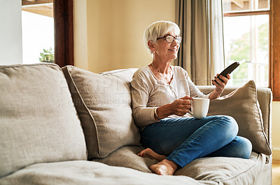 Buy stock photo Full length shot of a happy senior woman sitting alone on her sofa and holding a cup of coffee