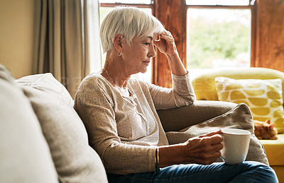 Buy stock photo Cropped shot of an attractive senior woman sitting on the sofa alone and suffering from a headache