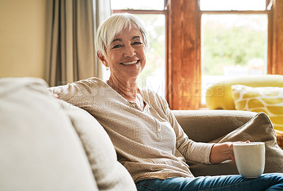Buy stock photo Cropped portrait of an attractive senior woman sitting alone on her sofa and holding a cup of coffee